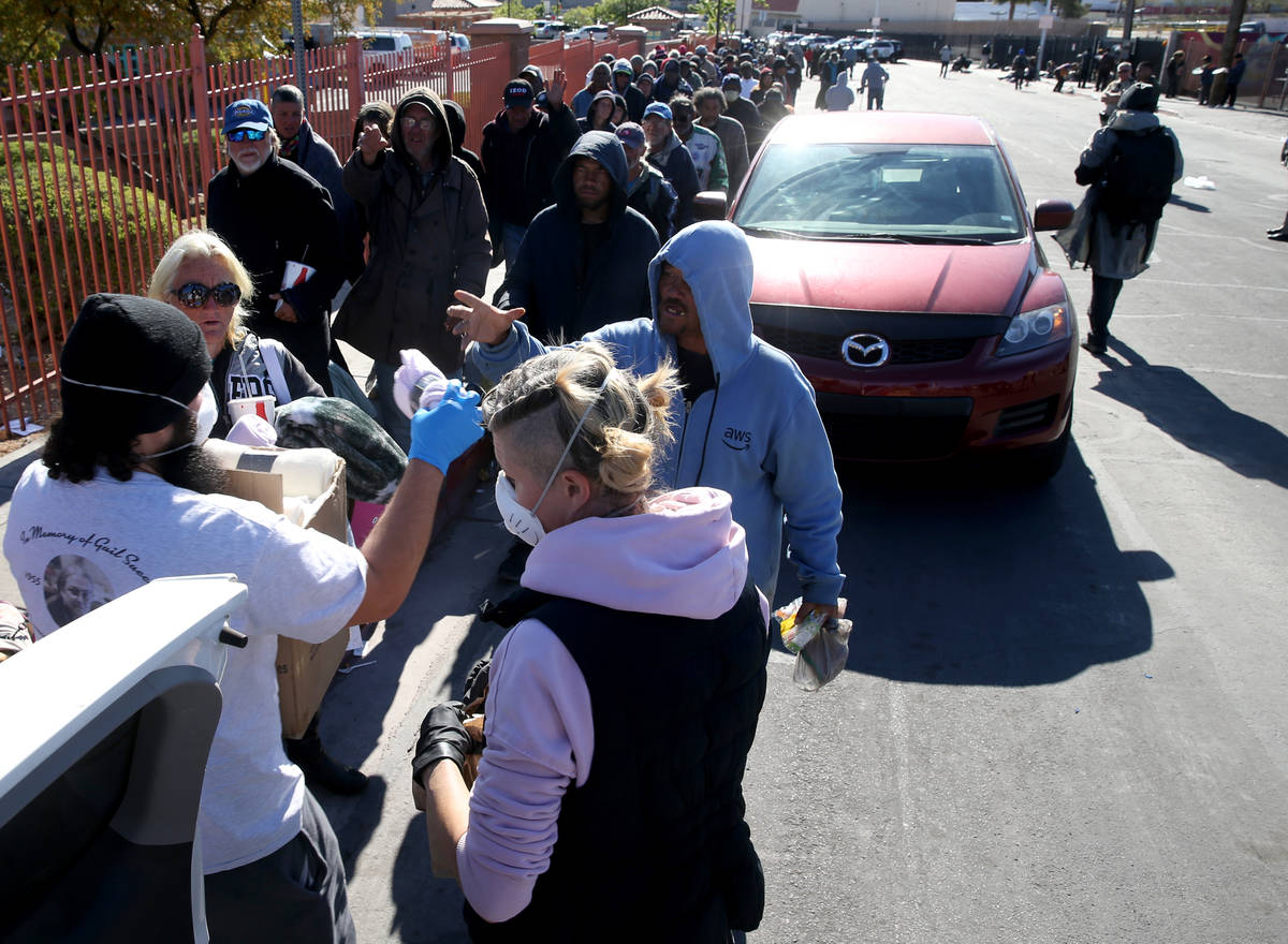 Joey Lankowski and Morgan Kozlowski of homeless outreach organization Food Not Bombs hand out b ...