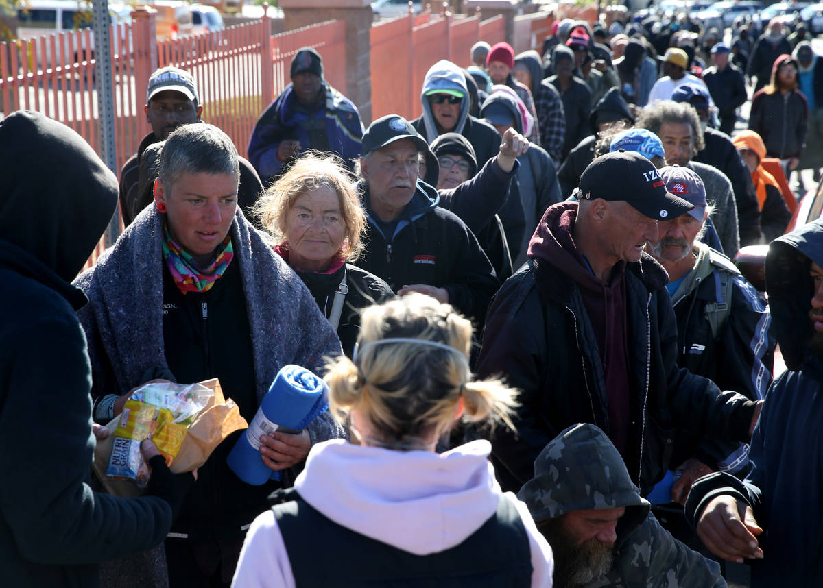People line up for sack lunches, hygiene kits and blankets from homeless outreach organization ...
