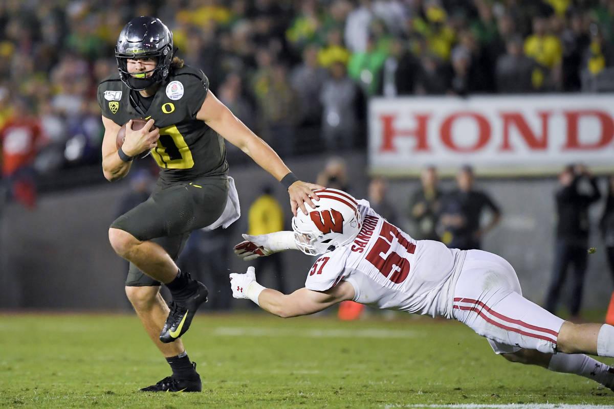 Oregon quarterback Justin Herbert runs for a touchdown past Wisconsin linebacker Jack Sanborn d ...