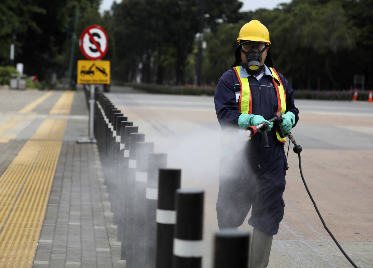 A worker sprays disinfectant at the pedestrian walkway at Senayan Sports Complex amid coronavir ...