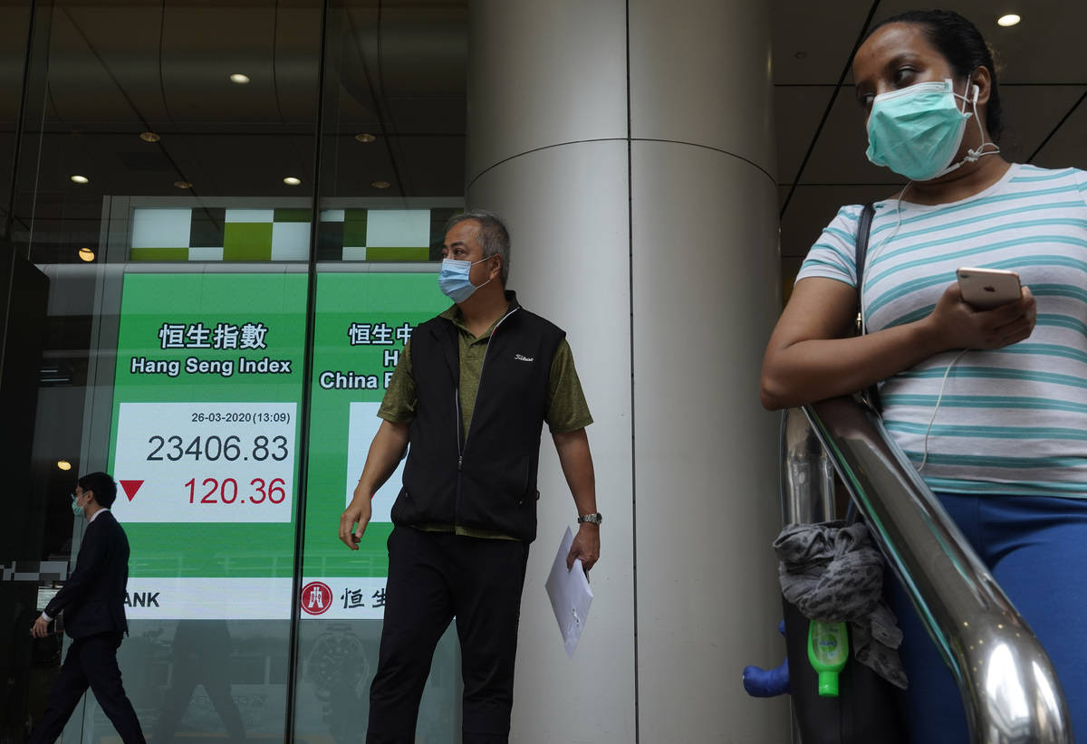 People wearing face masks walk past a bank electronic board showing the Hong Kong share index a ...
