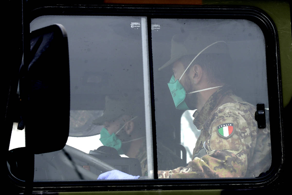 Military trucks moving coffins of deceased people leave the cemetery of Bergamo, one of the are ...