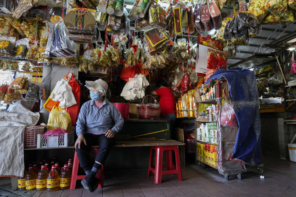 A vendor waits for customers at a market during the movement control order due to the outbreak ...