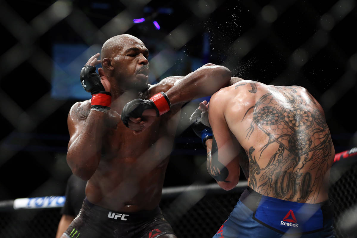 Jon Jones, left, throws an elbow against Anthony Smith in the light heavyweight title bout duri ...