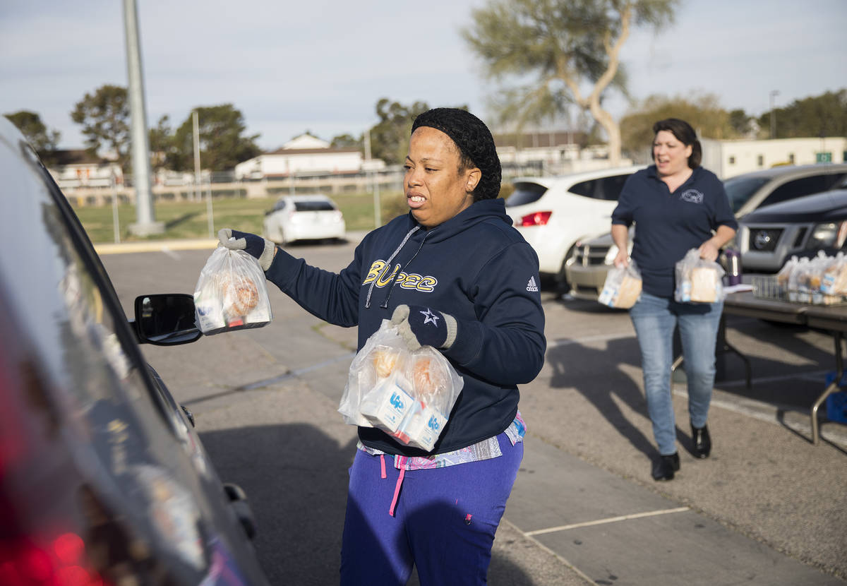 Clark County School District employees hand out breakfast and lunch packages to families at Cla ...
