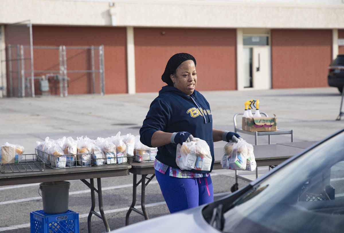 A Clark County School District employee hands out breakfast and lunch packages to families at C ...