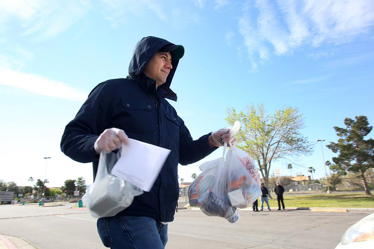 Clark County School District employee Miguel Zazueta helps pass out food and homework assignmen ...