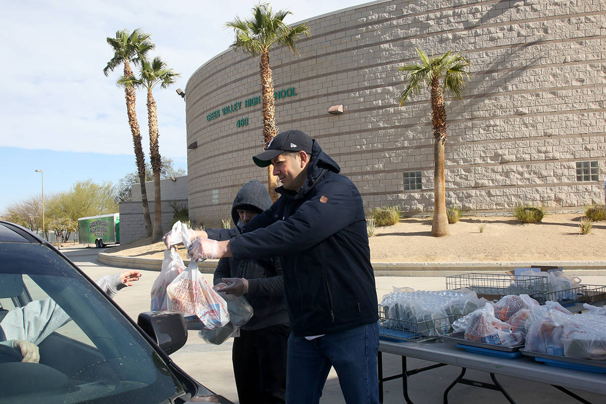 Clark County School District employees Miguel Zazueta, right, and Greggy Malimban help pass out ...
