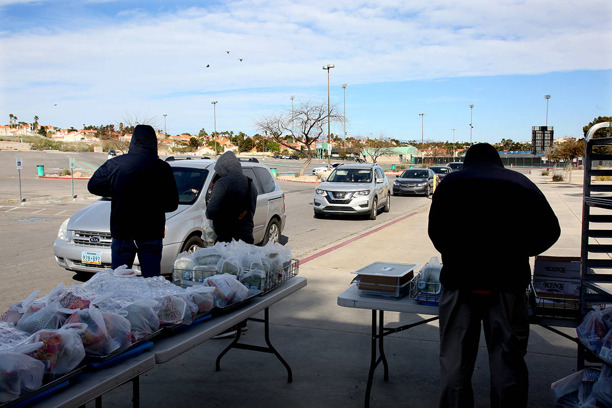 Clark County School District employees help pass out food and homework assignments at Green Val ...