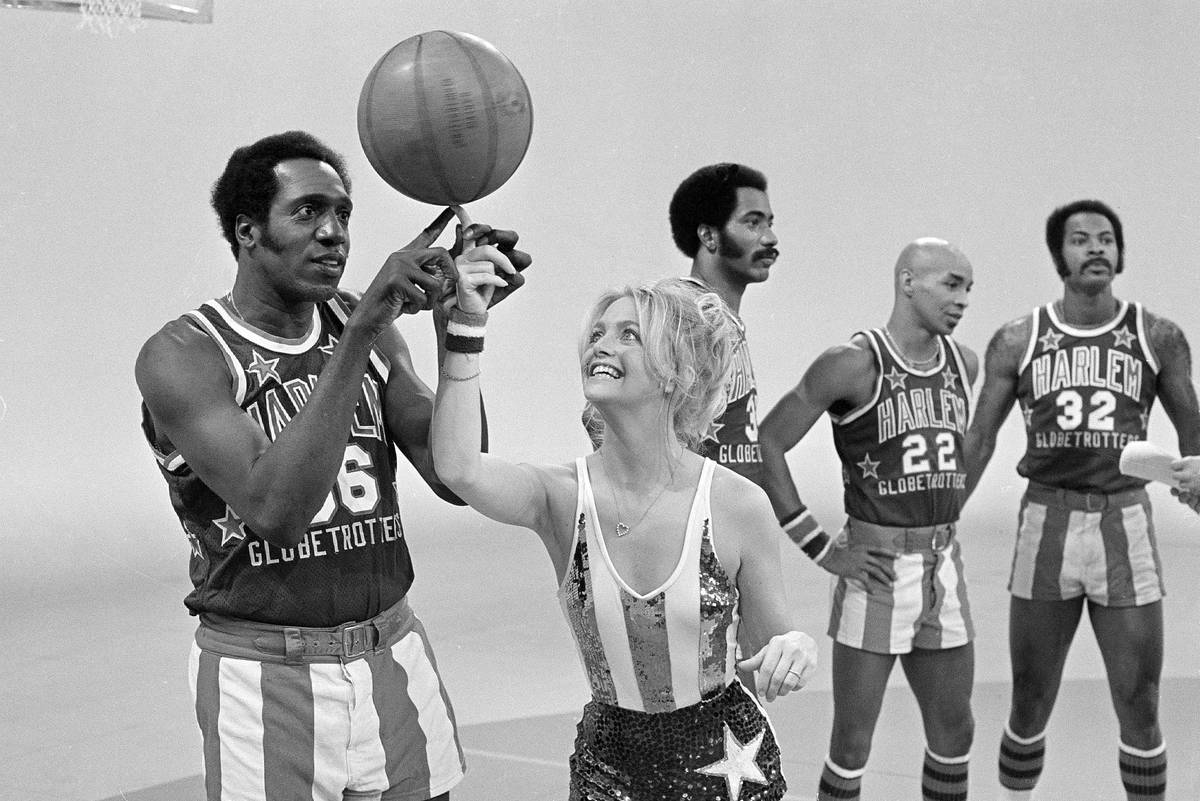Actress Goldie Hawn has her finger guided to the basketball by Harlem Globetrotters' Meadowlark ...