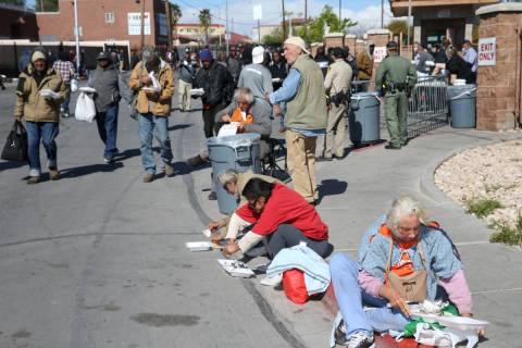 People eat to-go lunches from Catholic Charities on Foremaster Lane in Las Vegas Thursday, Marc ...