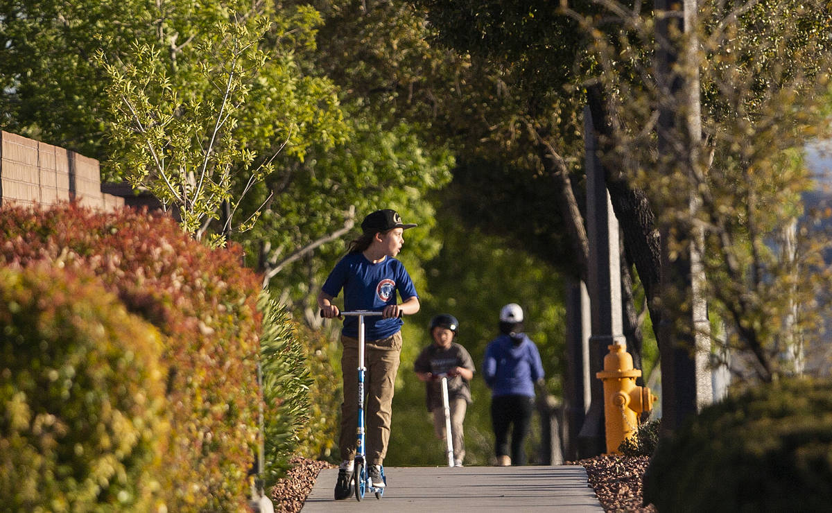 Children ride their scooters on North Hualapai Way on Friday, March 27, 2020, in Las Vegas. (Be ...