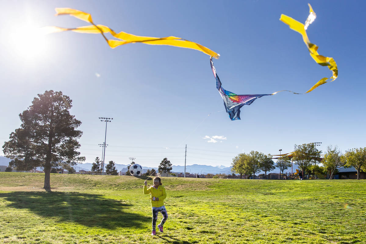 People take advantage of the open space at Desert Breeze Park flying kites on Friday, March 27, ...