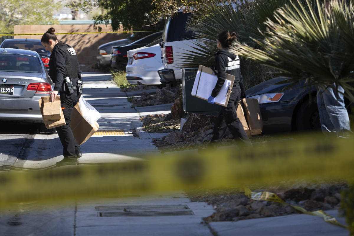 Members of Las Vegas police's crime scene investigative unit carry evidence out of the house wh ...