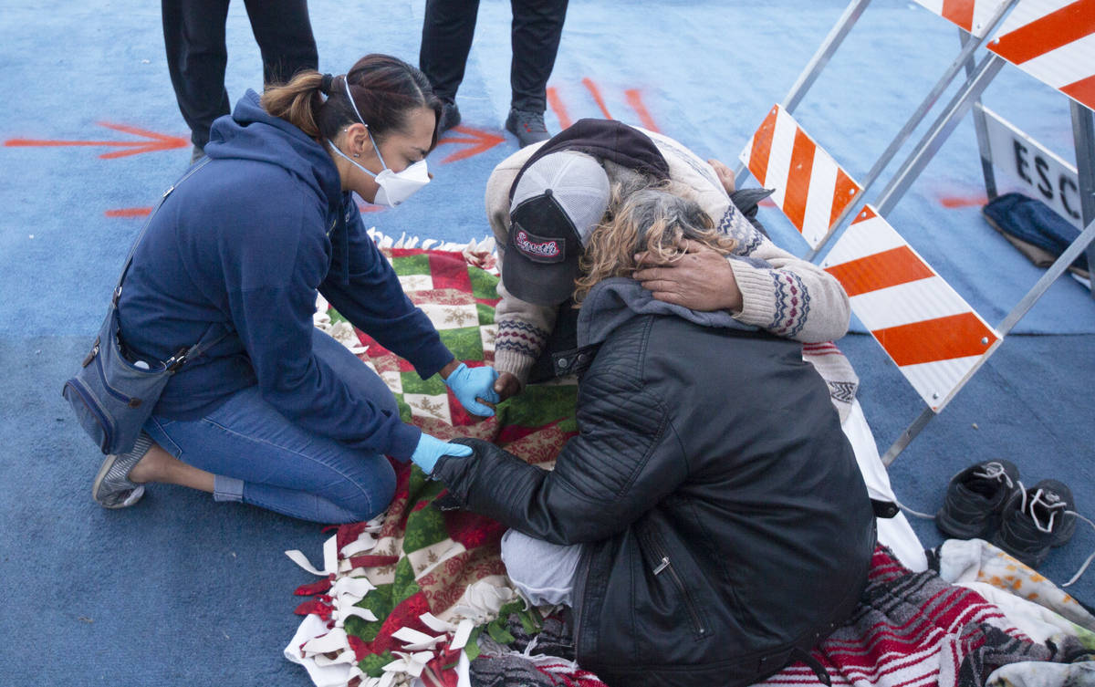 Katherine Kintner, with Messages of Faith Ministry, leads a homeless couple in prayer at a temp ...