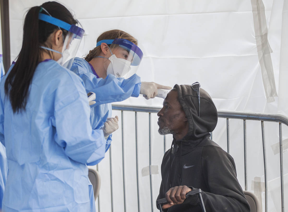 Touro University Nevada medical student Allison Moran, middle, take Charles Maenson's temperatu ...