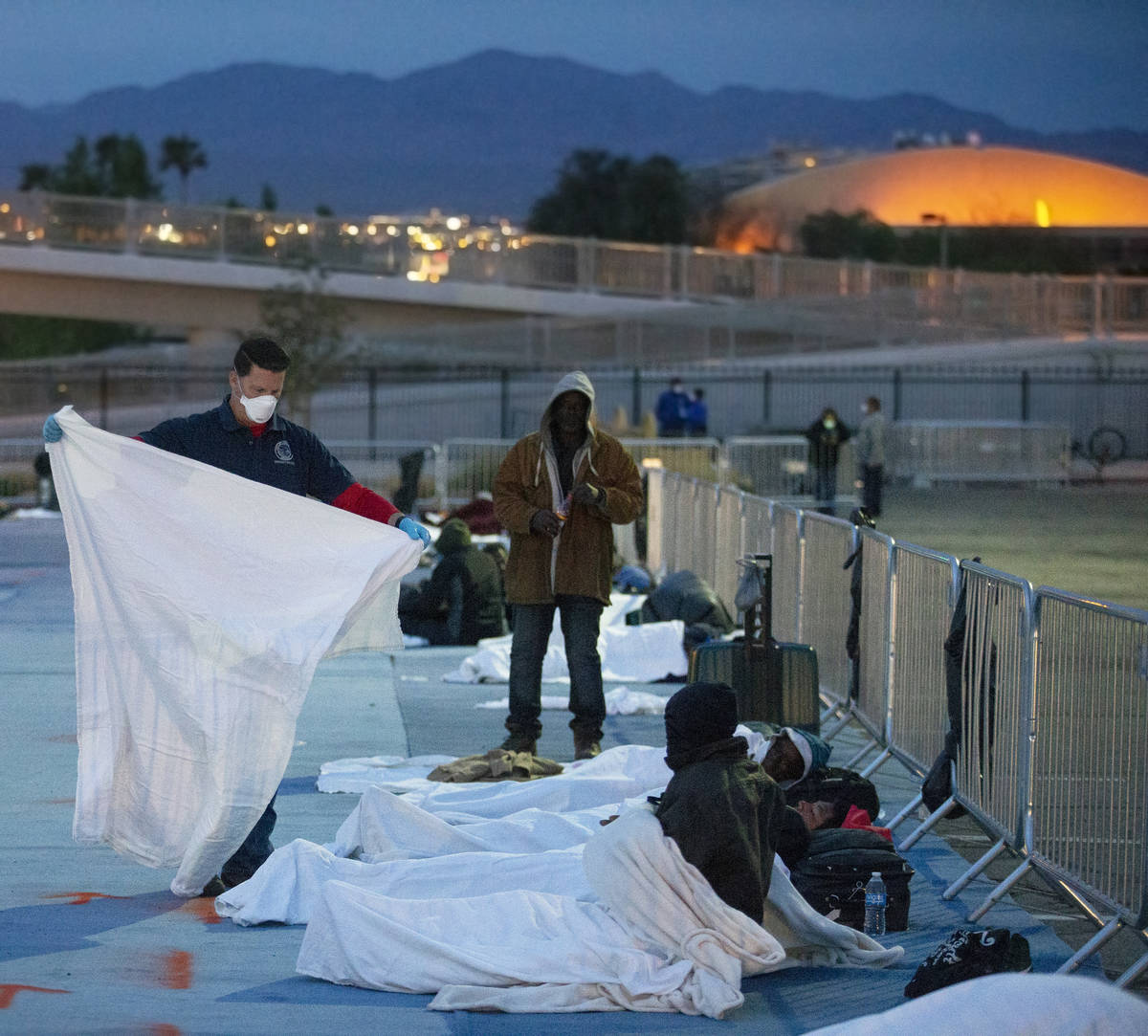Volunteers provide extra blankets to the homeless at a temporary shelter at the upper parking l ...