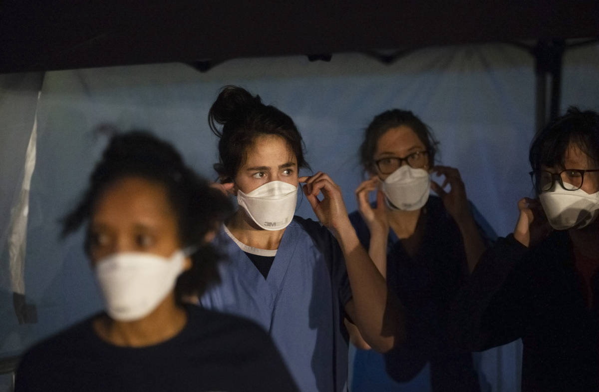 Touro University Nevada medical students work in a coronavirus screening station at a temporary ...