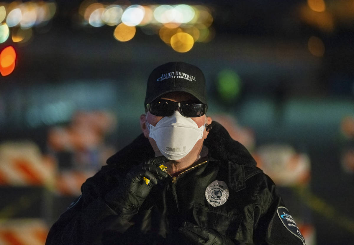 Allied Universal Security officer Jeff Reinharcz guards the entrance to a temporary shelter for ...