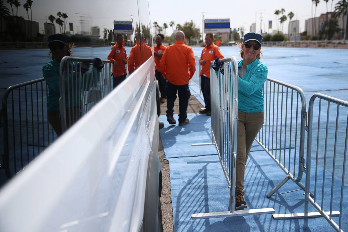 Rhonda Giannini, volunteer with Teamsters Local 631, helps to set up barriers for a temporary h ...