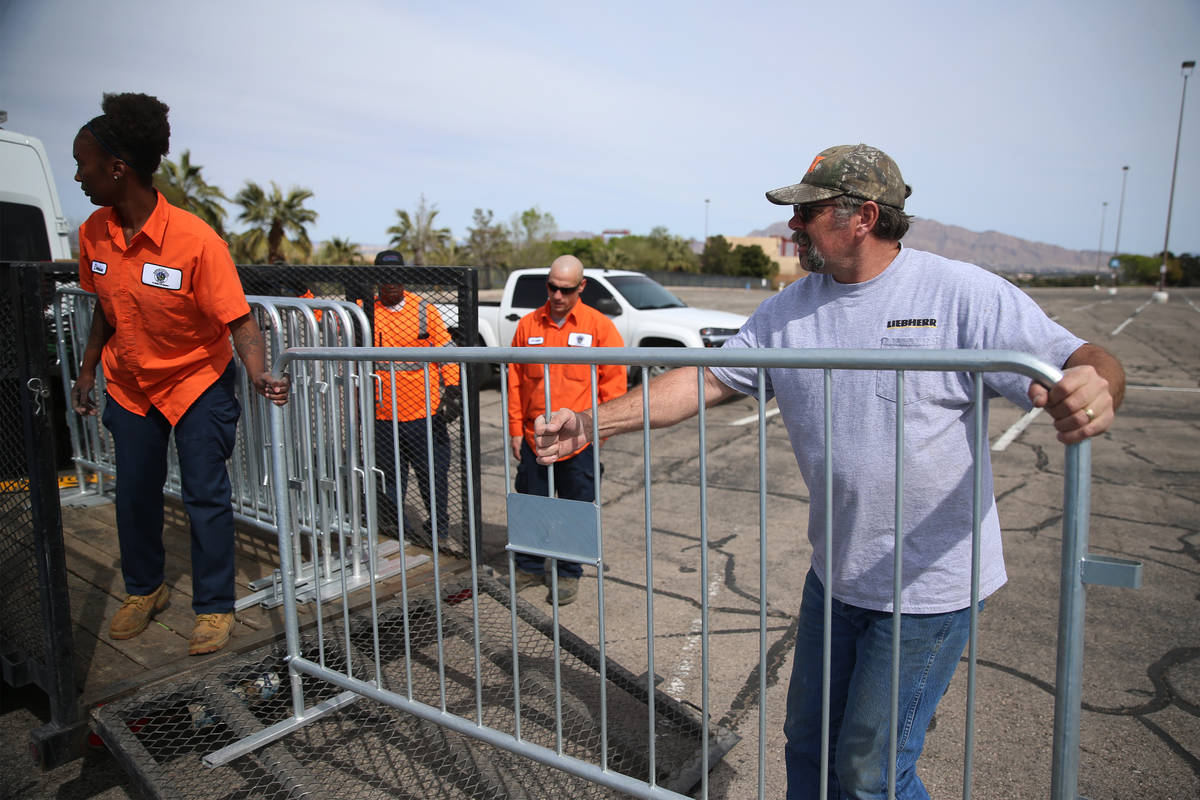 John Grul, right, volunteer with Teamsters Local 631, helps to set up barriers for a temporary ...