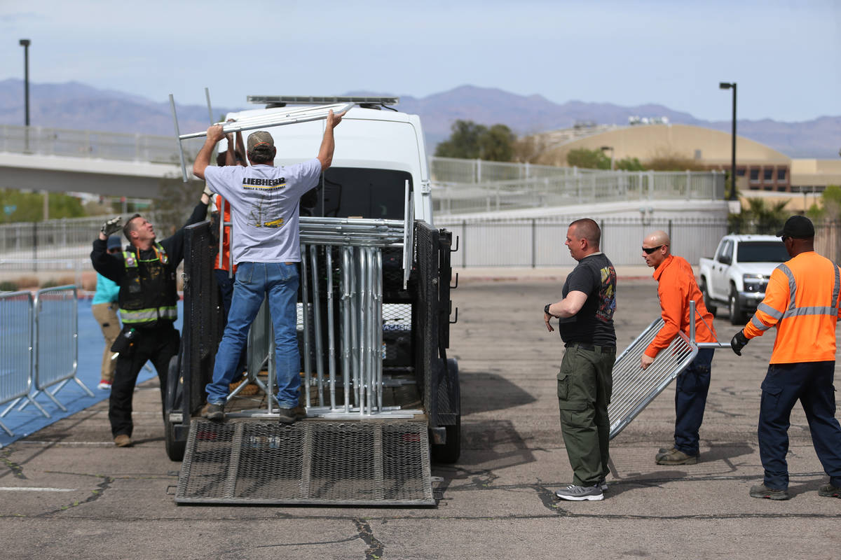 Volunteers set up barriers for a temporary homeless shelter at the Cashman Field parking lot in ...