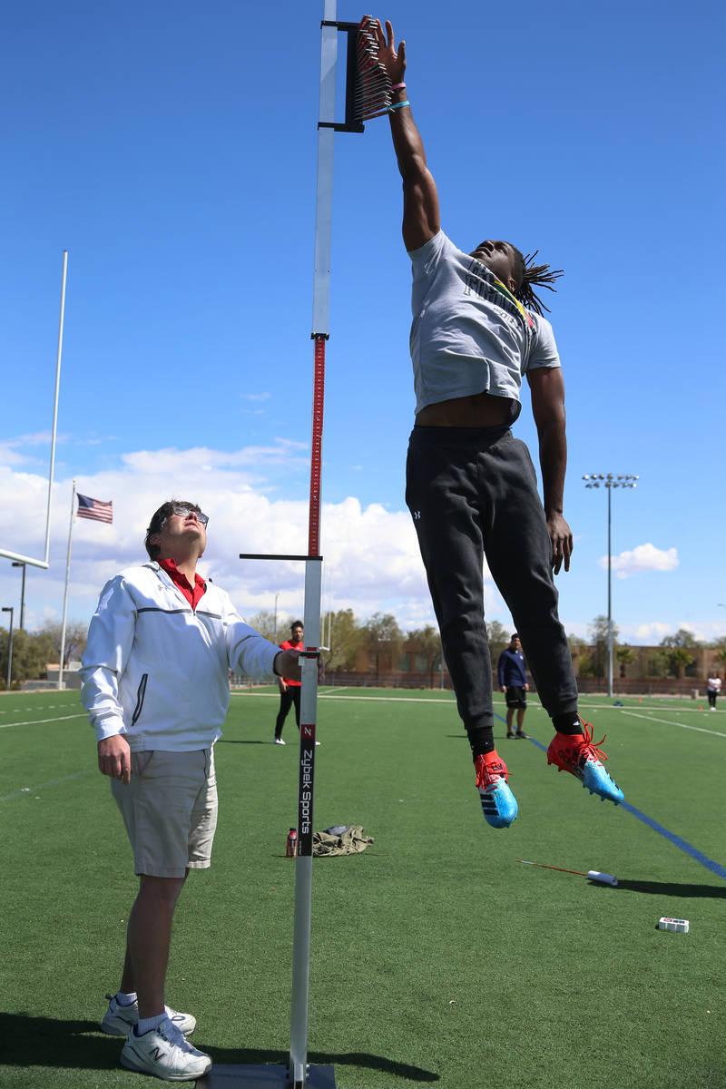 University of Hawai'i football graduate Ikem Okeke, right, leaps for the vertical jump test as ...