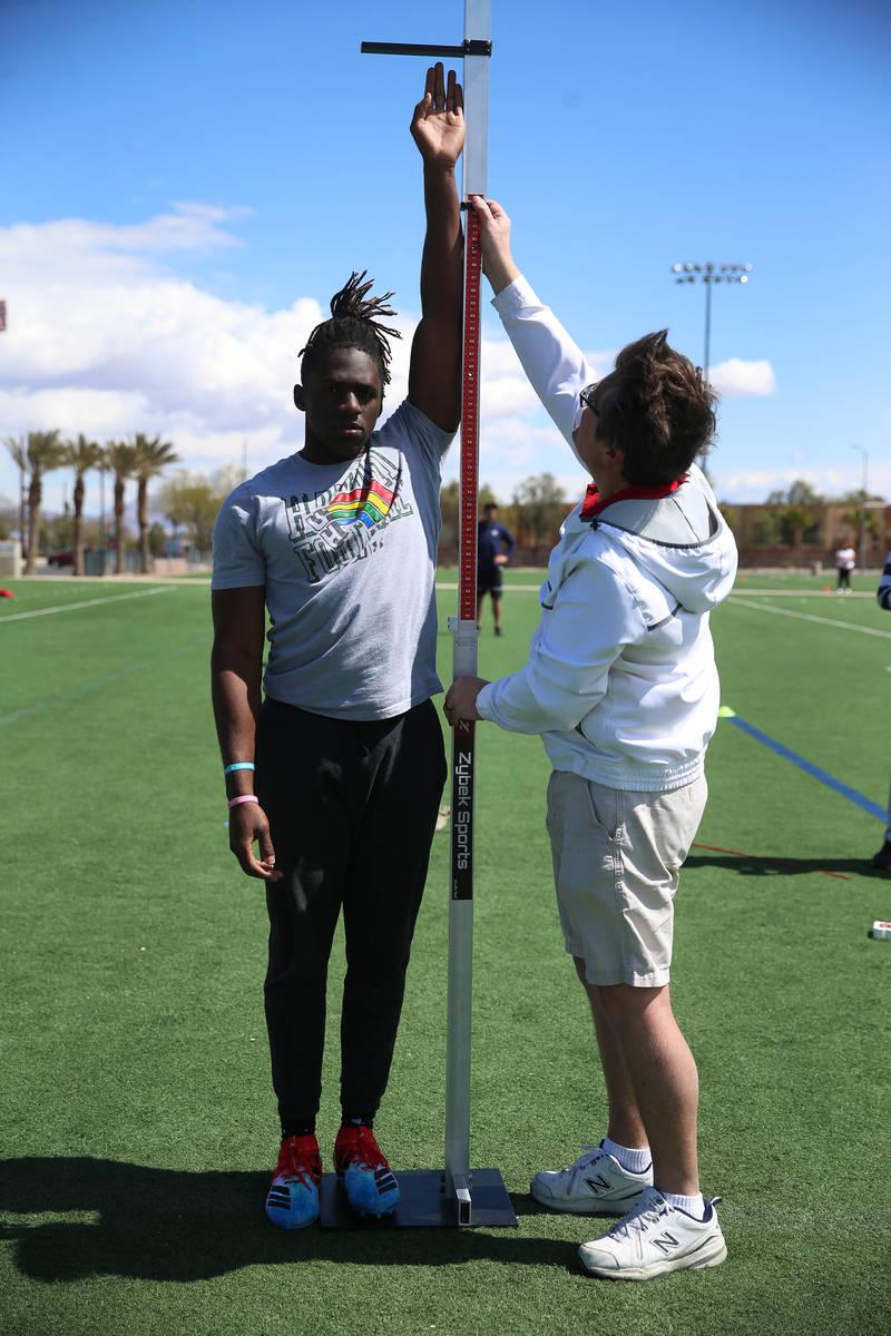 University of Hawai'i football graduate Ikem Okeke, left, gets his reach measured by Mike Weins ...