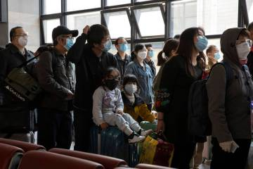 Travelers wearing face masks to help curb the spread of the coronavirus line up for their train ...