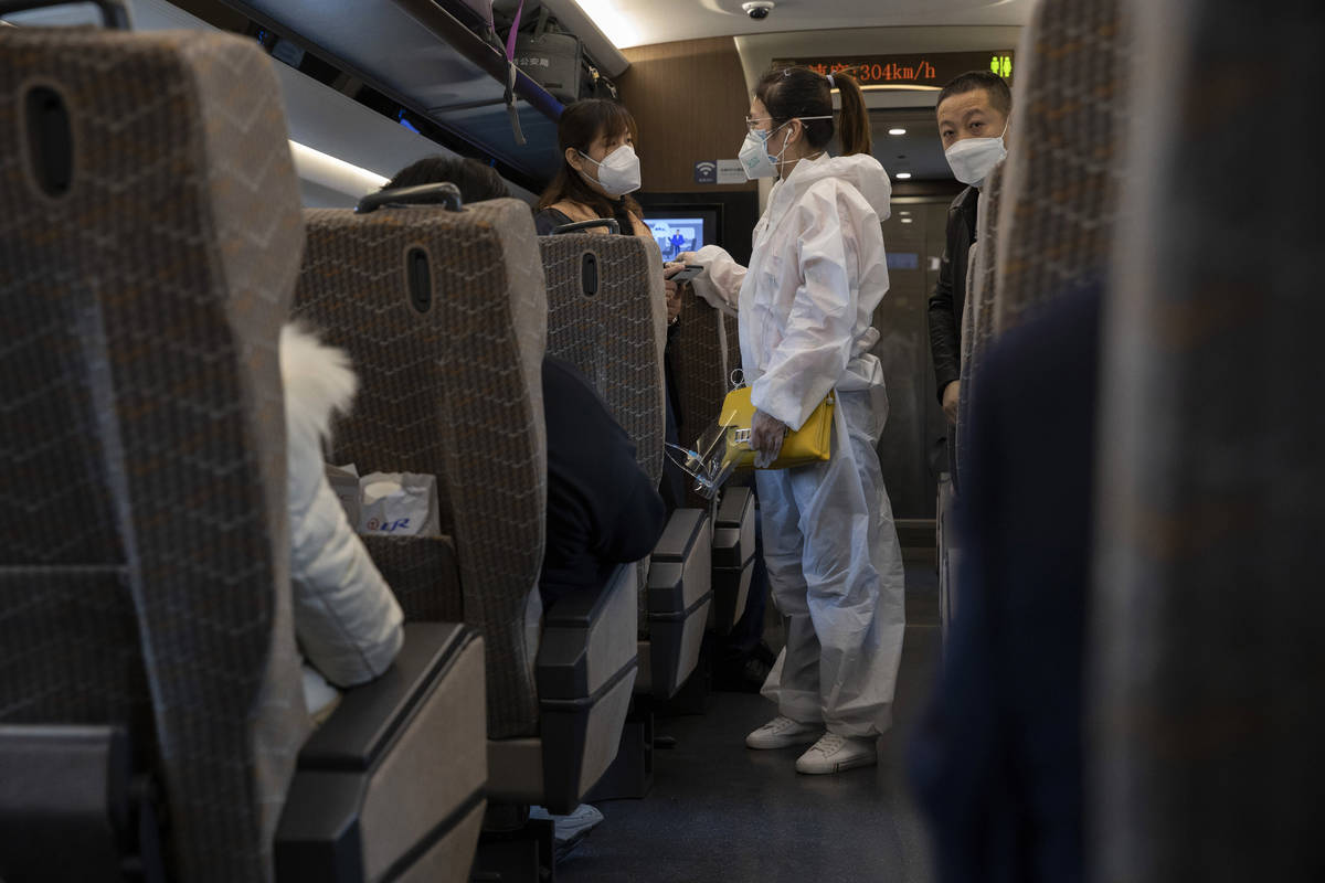 A traveler wearing a protective suit chats with another onboard a train leaving from the train ...