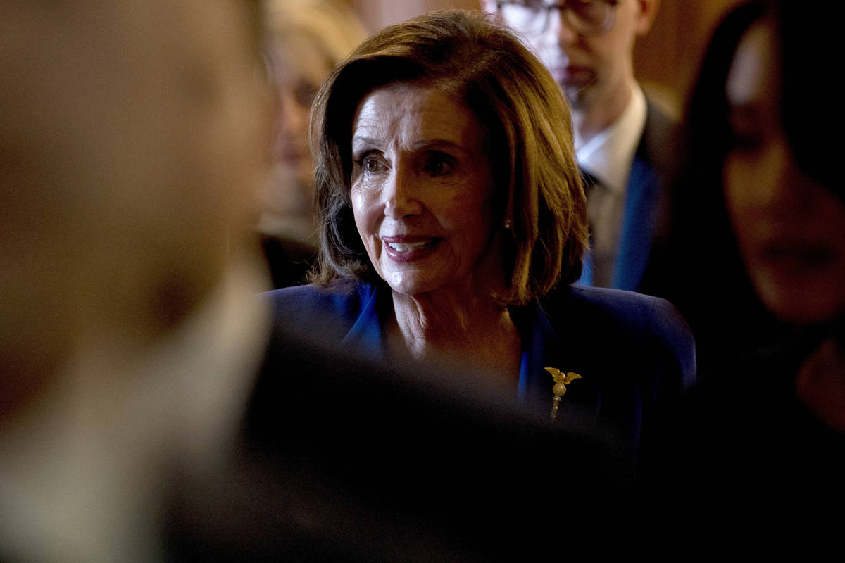 House Speaker Nancy Pelosi of Calif., walks to her office after signing the Coronavirus Aid, Re ...