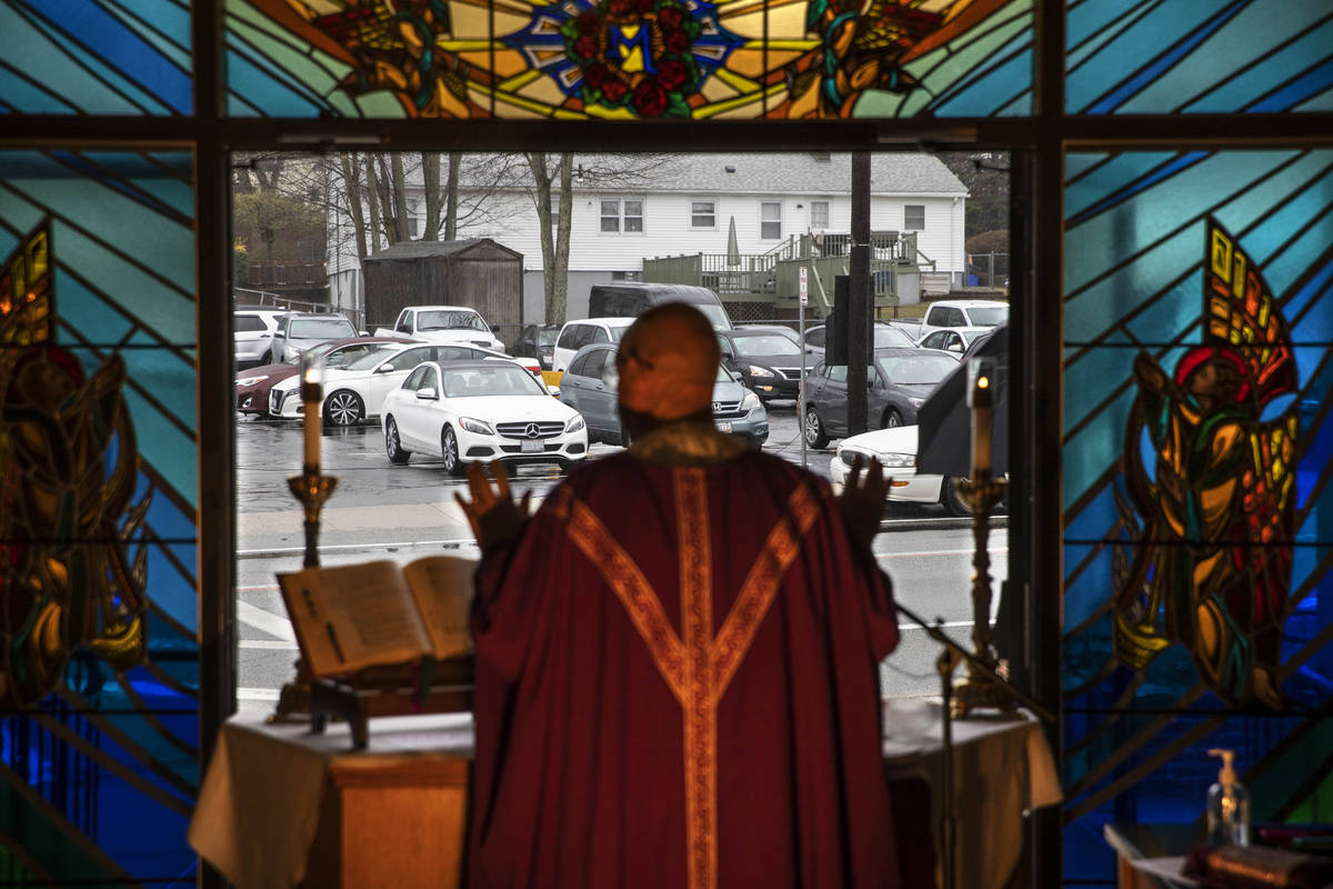 Rev. Peter Gower celebrates Mass from the front door of Our Lady of Grace Catholic Church as wo ...