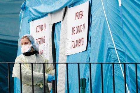 A medical worker prepares to reenter a COVID-19 testing tent set up outside Elmhurst Hospital C ...