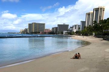 A couple rests on an empty section of Waikiki Beach in Honolulu on Saturday, March 28, 2020. (A ...
