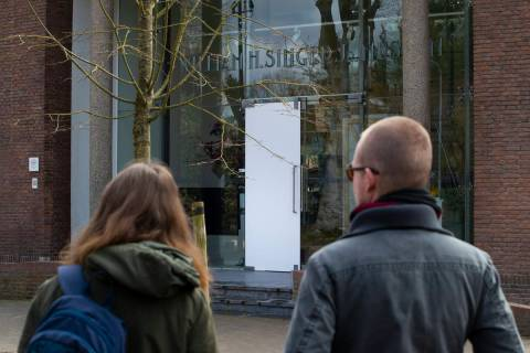 Two people look at the glass door which was smashed during a break-in at the Singer Museum in L ...