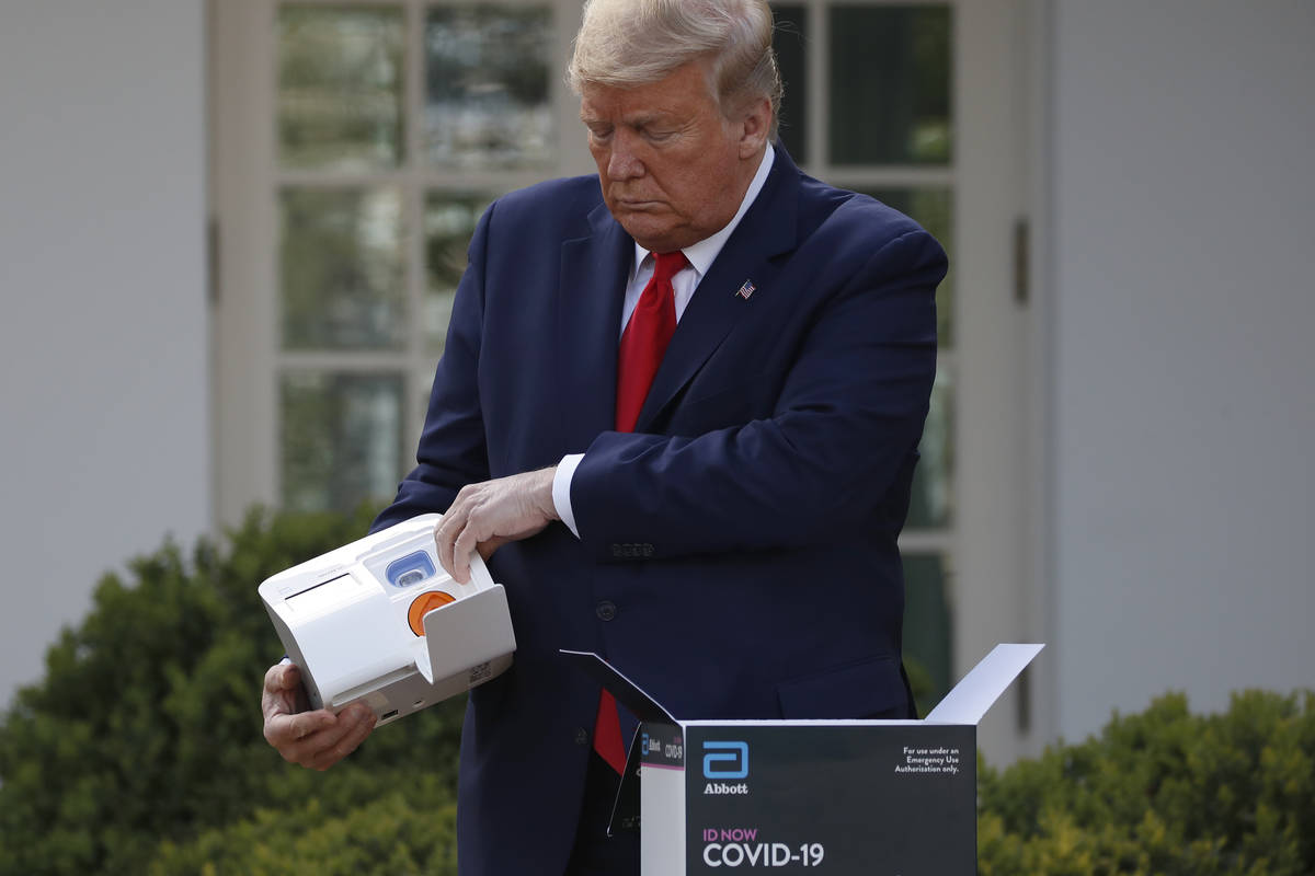 President Donald Trump opens a box containing a 5-minute test for COVID-19 from Abbott Laborato ...