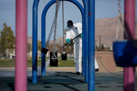 A worker cleans and disinfects playground equipment due to the coronavirus outbreak at a park W ...