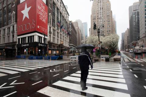 In a Monday, March 23, 2020, file photo, a man crosses the street in front of Macy's, in New Y ...