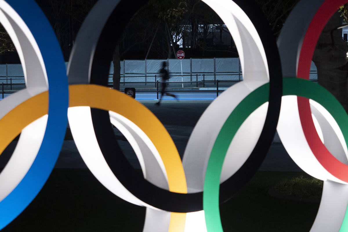 A man jogs past the Olympic rings Monday, March 30, 2020, in Tokyo. The Tokyo Olympics will ope ...