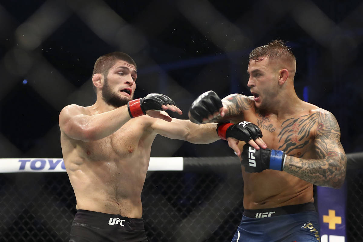 Russian UFC fighter Khabib Nurmagomedov, left, fights with UFC fighter Dustin Poirier, of Lafay ...
