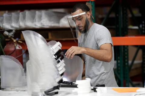 Jonathon Pedrosa, an employee at Faulkner Plastics, assembles plastic face shields used for inf ...