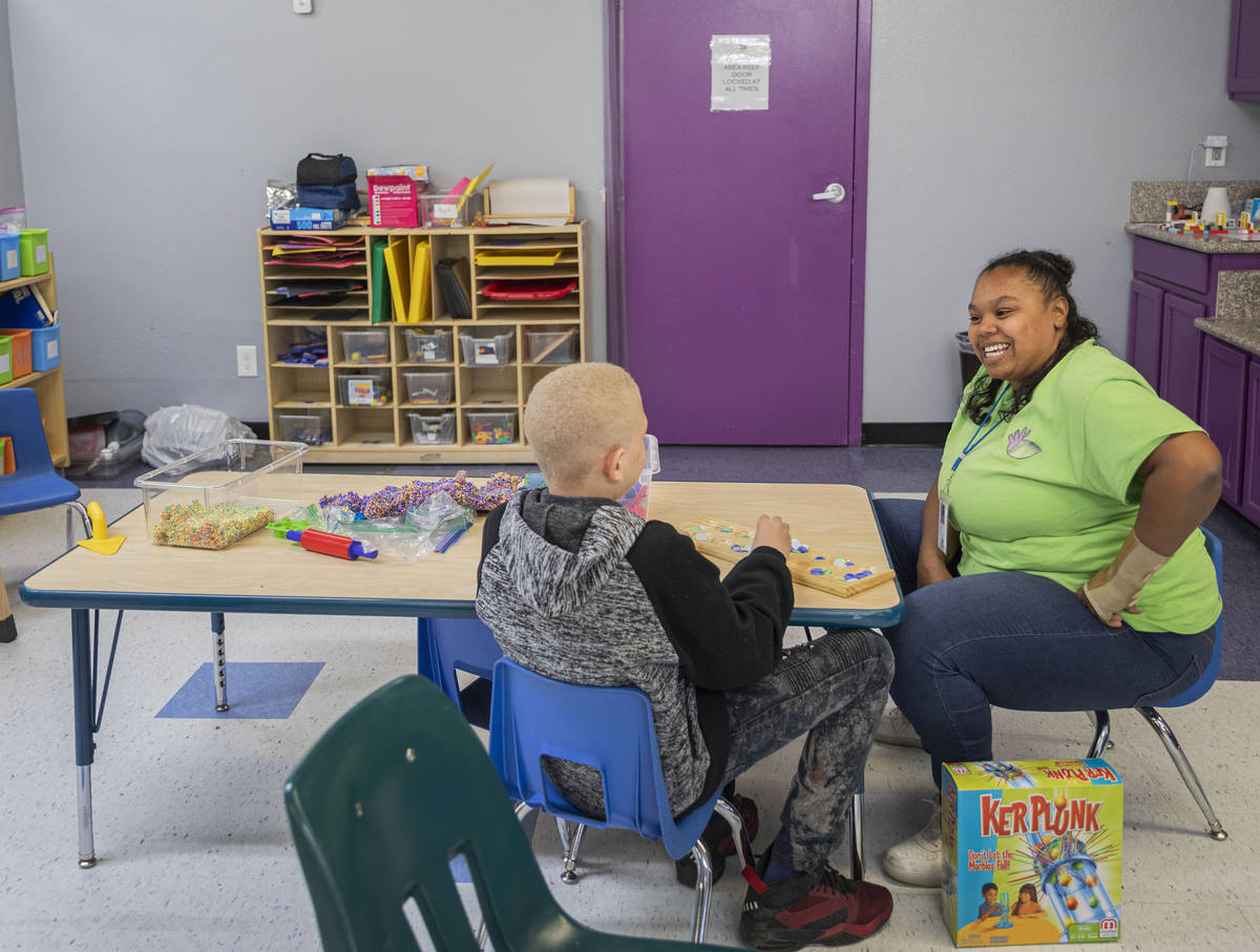 Nysir Darby, 10, plays a game with assistant teacher Nia Spinner in the school aged room at the ...
