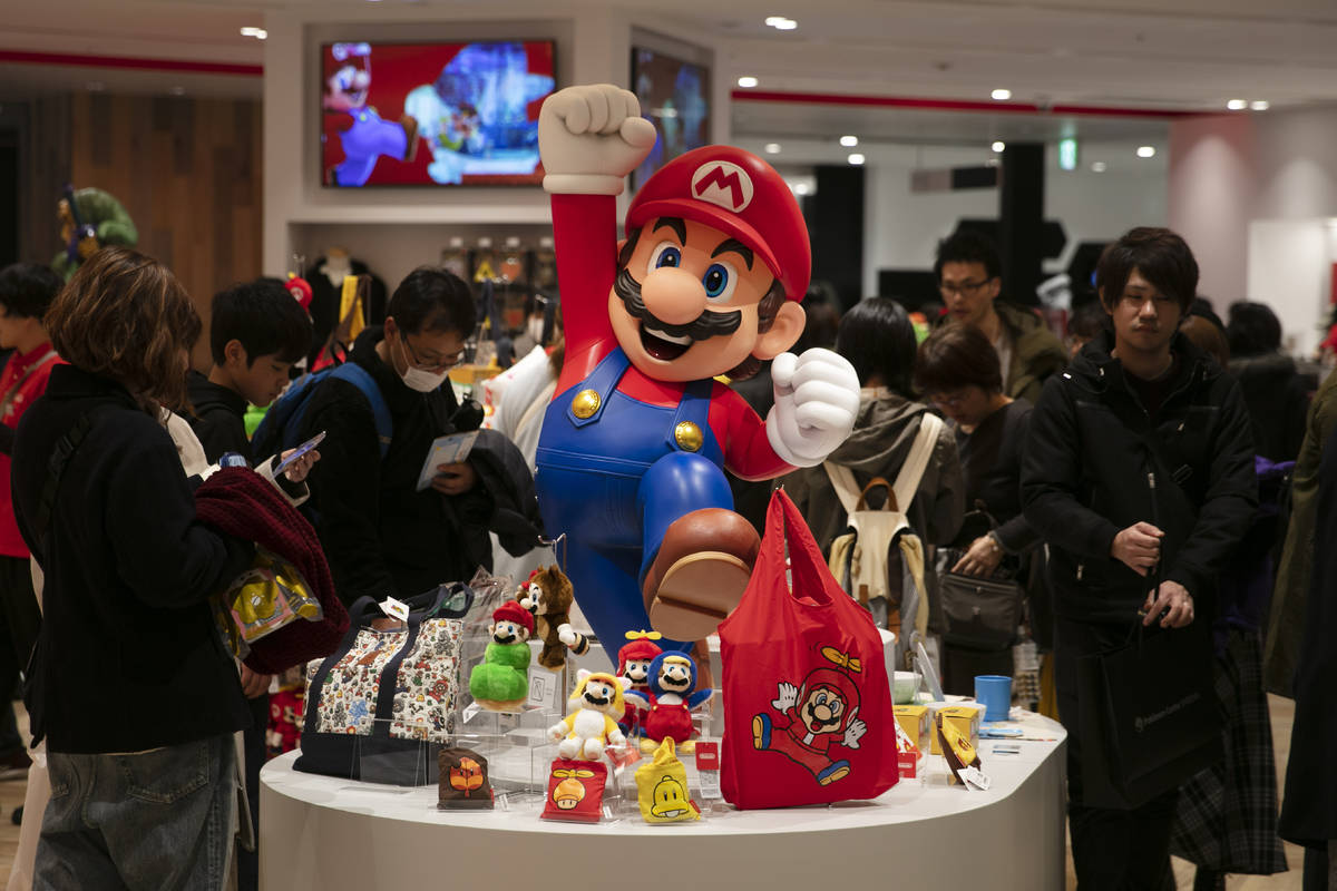 In this Jan. 23, 2020, photo, a Super Mario figure is on display as people shop at Nintendo's o ...