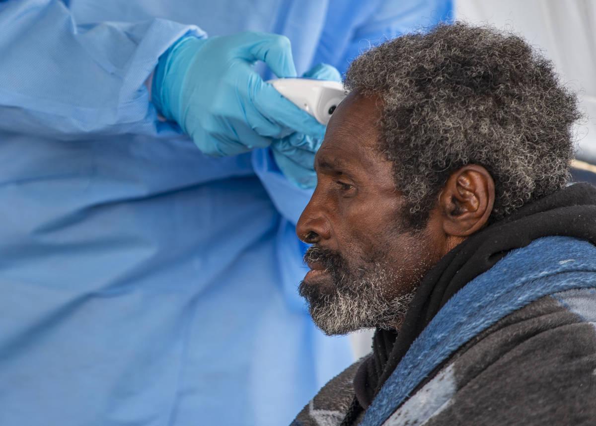 A homeless man has his temperature checked by Touro University Nevada medical student Sami Musa ...