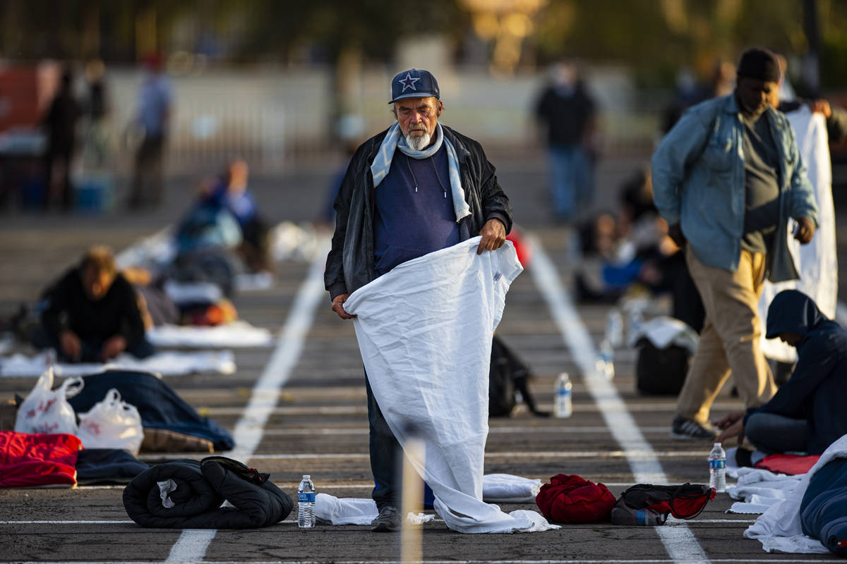 A homeless man sets up in an individual space at a temporary shelter in the upper parking lot a ...