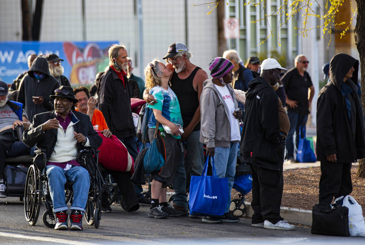Homeless people line up to be screened to enter a temporary shelter in the upper parking lot at ...