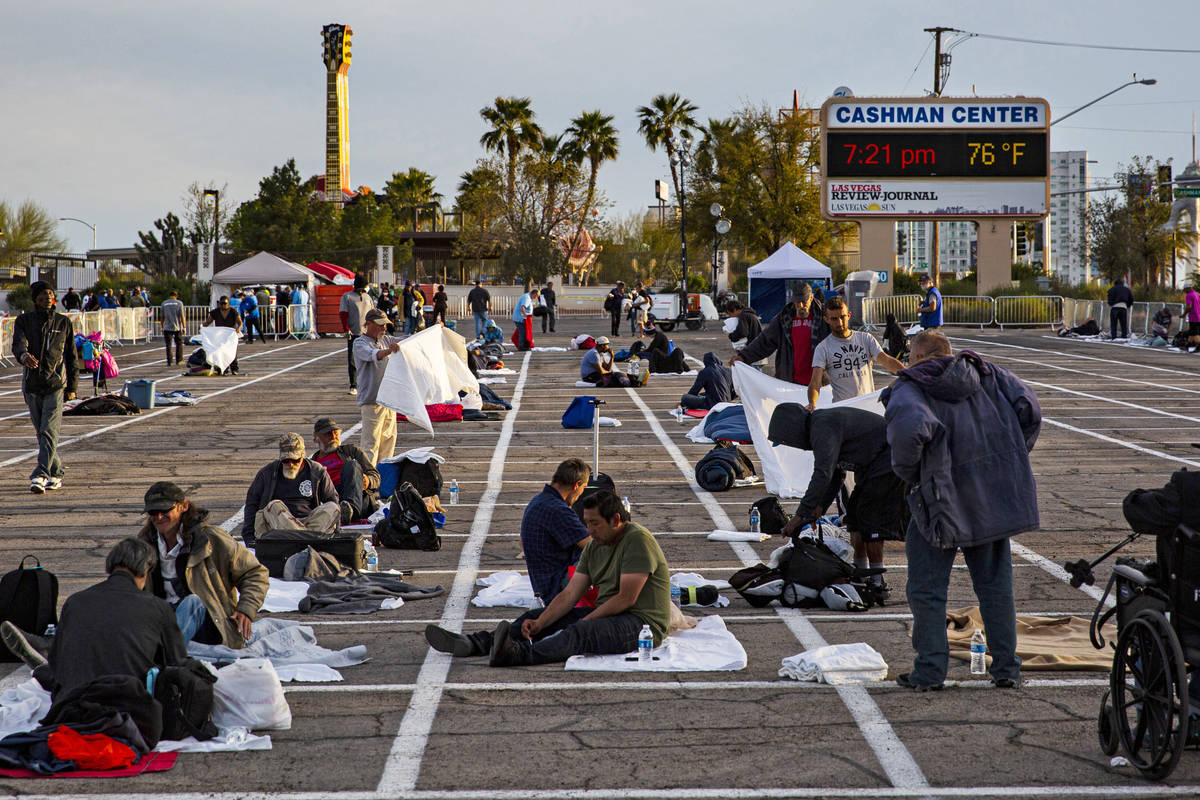 Homeless people get set up in their individual spaces at a temporary shelter in the upper parki ...