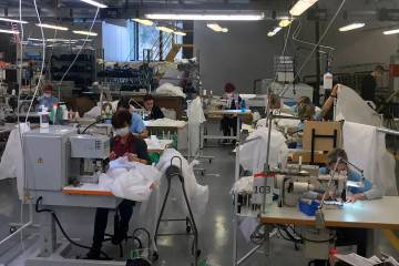 In this photo released Monday, March 30, 2020, workers at the Armani factory in Trento, Italy, ...