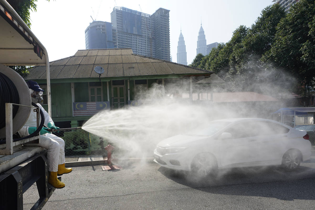 Health officials spray disinfectant in a Kampung Baru, traditional Malay village, in Kuala Lump ...