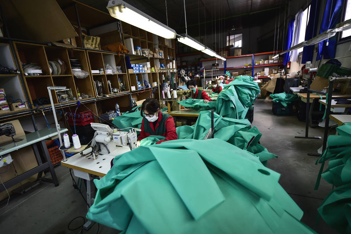 Volunteer workers in a clothing factory manufacturing firefighting gear, make hospital gowns fo ...
